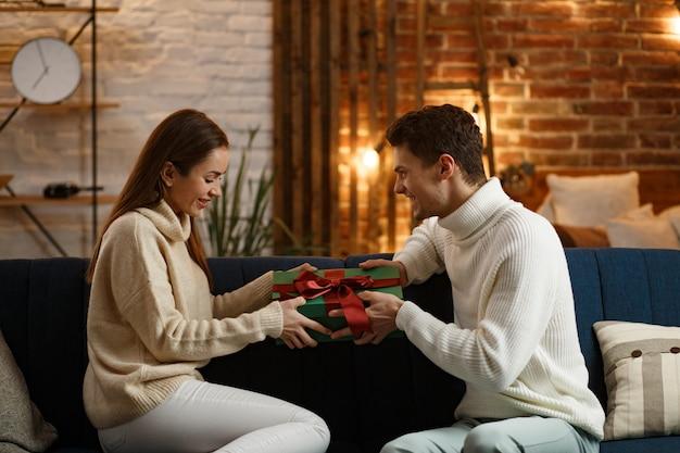 Knappe man die een geschenk presenteert aan zijn mooie meisje en glimlacht. mooie jonge paar thuis genieten van tijd samen doorbrengen. wintervakantie, kerstvieringen, nieuwjaarsconcept.