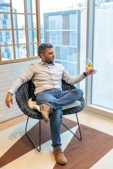 Knappe man die een glas witte wijn proeft terwijl hij in zijn woonkamer zit