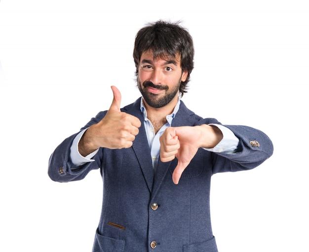 Knappe man die een goed-slecht teken op een witte achtergrond maakt