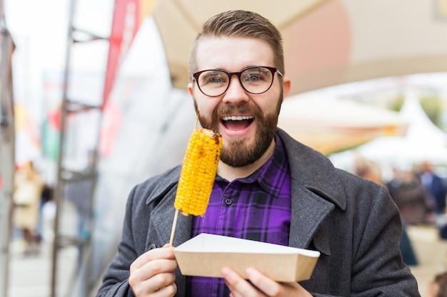 Knappe man die een heerlijke maïskolf op straat eet.