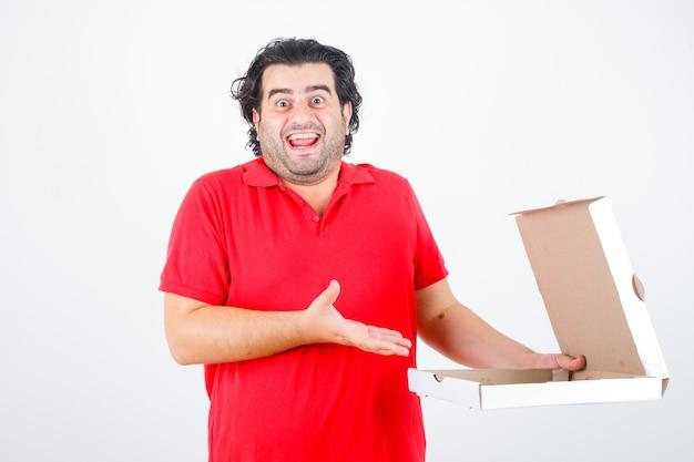 Knappe man die een papieren doos opent, de hand er op een vrolijke manier naar toe uitstrekt in een rood t-shirt en er vrolijk uitziet. vooraanzicht.