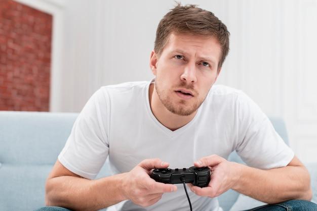 Knappe man die een spel speelt met een controller