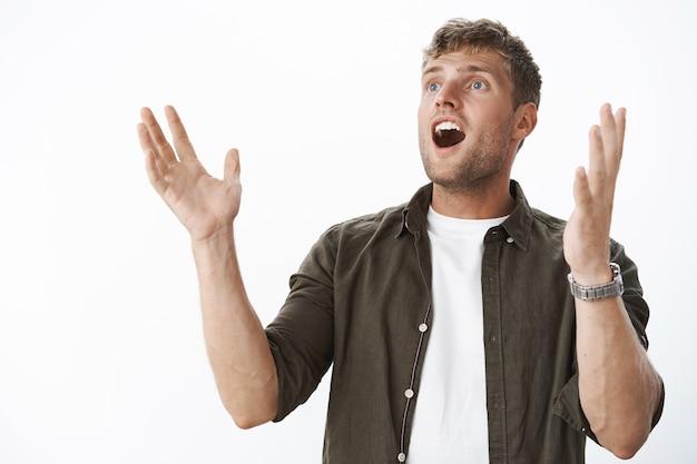 Knappe man die getuige is van een wonder vlak voordat ogen de kaak laten vallen van opwinding en verbazing, handen opstekend hoopvol en onder de indruk kijkend verbaasd naar de linkerbovenhoek over de grijze muur