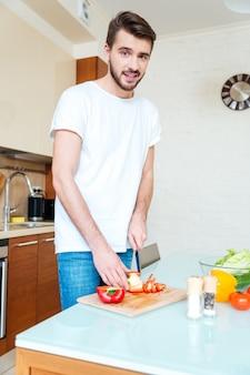 Knappe man die groenten snijdt in de keuken