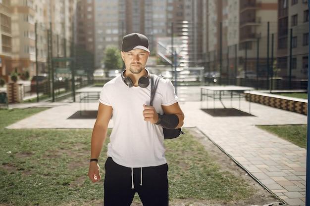 Knappe man die in een park met een koptelefoon