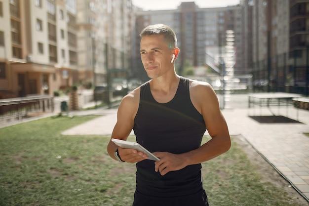 Knappe man die in een park met oortelefoons en een tablet