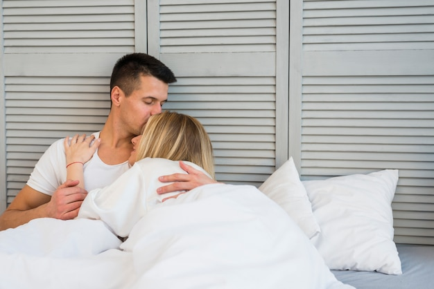 Knappe man die jonge vrouw kust die op bed ligt