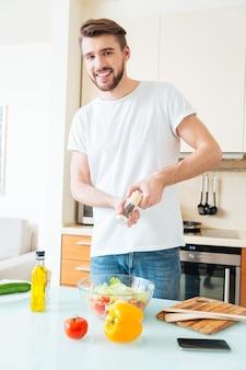 Knappe man die kruiden in salade toevoegt in de keuken en naar de voorkant kijkt