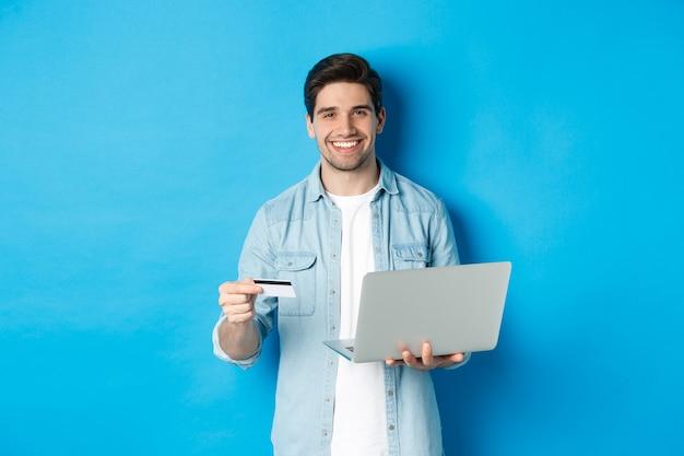 Knappe man die lacht, online winkelt en voor product betaalt, creditcard met laptop vasthoudt, over blauwe achtergrond staat.