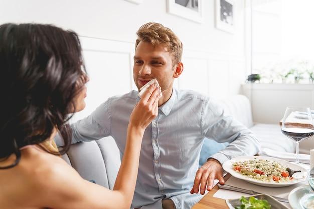 Knappe man die naar vriendinnen kijkt en glimlacht terwijl ze saus uit zijn mondhoek haalt
