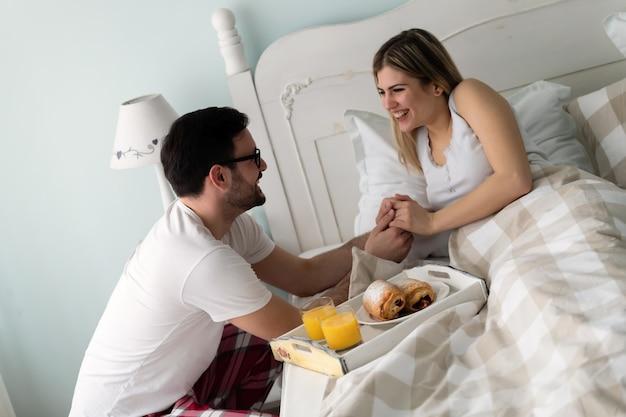 Knappe man die ontbijt naar zijn mooie vriendin in bed brengt