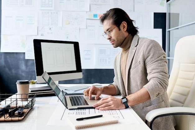 Knappe man die op laptop werkt