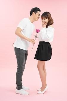 Knappe man die rode roos geeft aan zijn verraste vriendin.