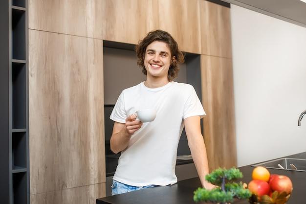 Knappe man die 's ochtends koffie drinkt in de keuken