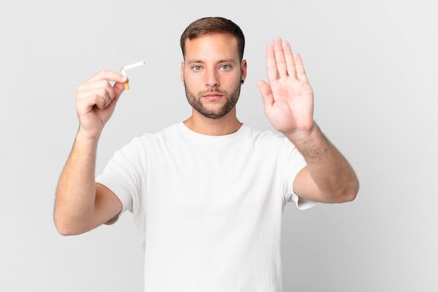 Knappe man die stopt met roken met een gebroken sigaar