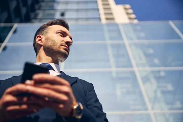 Knappe man die tijd alleen doorbrengt in de buurt van een groot zakencentrum terwijl hij zijn mobiele telefoon in handen houdt