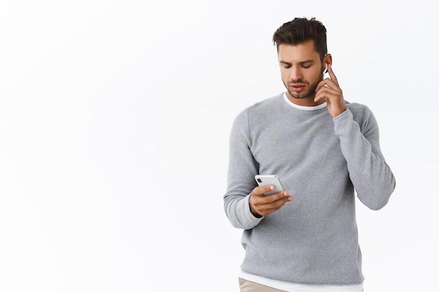 Knappe man die zich klaarmaakt om het kantoor te verlaten, draadloze koptelefoon op te zetten, volume aanraakkoptelefoon te verhogen, smartphone vast te houden, mobiel scherm te kijken terwijl de instellingen van de oordopjes worden gewijzigd, witte muur