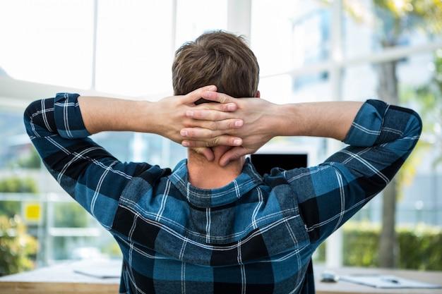 Knappe man die zijn armen in een helder kantoor uitstrekt