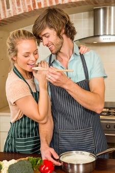 Knappe man die zijn vriendin maakt de voorbereiding in de keuken proeven