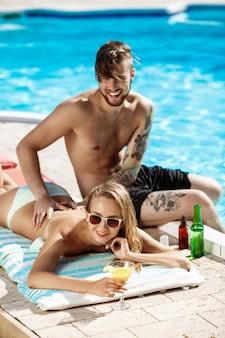 Knappe man die zonnebrandroom toepassen op vrouwen dichtbij zwembad