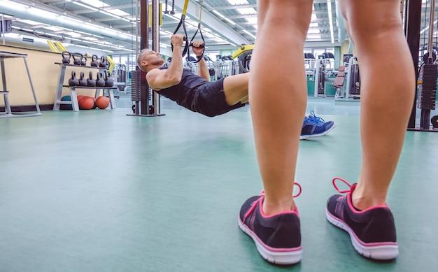 Knappe man doet harde schorsing training met fitness bandjes en vrouwelijke benen op de voorgrond.