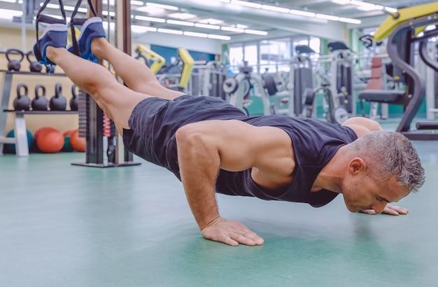 Knappe man doet harde schorsing training met fitness bandjes in een fitnesscentrum. gezond en sportief levensstijlconcept.