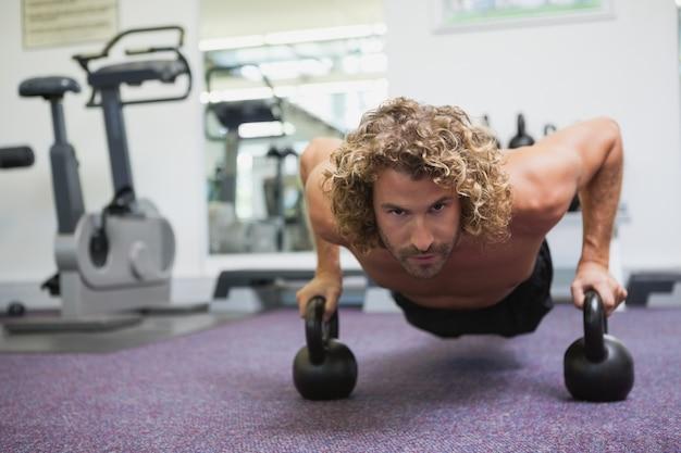 Knappe man doet push ups met waterkoker klokken in de sportschool