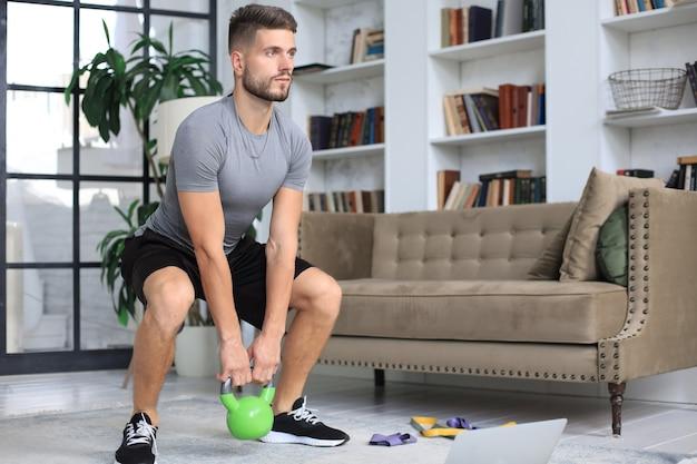 Knappe man doet sportoefening met kettlebell thuis. concept van gezond leven.