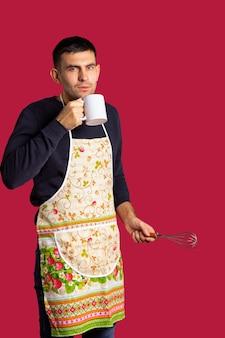 Knappe man drinkt thee tijdens het koken in de keuken met een garde in zijn hand