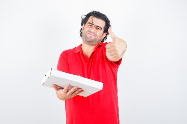 Knappe man duim opdagen, papieren doos in rood t-shirt vasthouden en op zoek vrolijk, vooraanzicht.