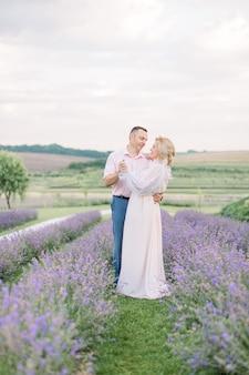 Knappe man en elegante mooie blonde dame, daten en samen wandelen buiten in lavendelveld