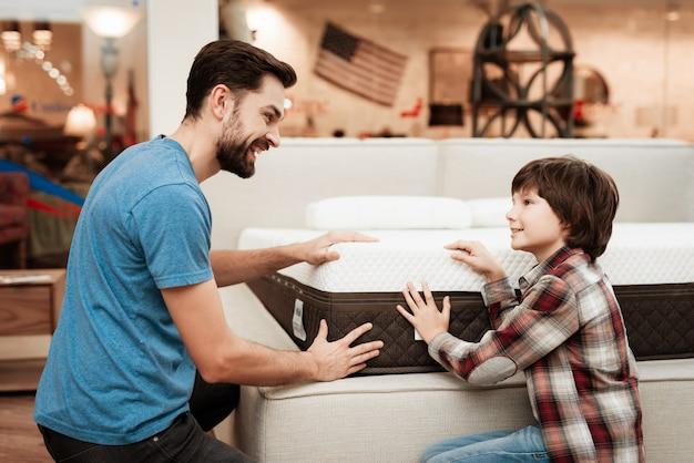 Knappe man en kleine jongen kiezen matras