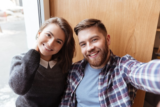 Knappe man en mooi meisje selfie maken bij het raam