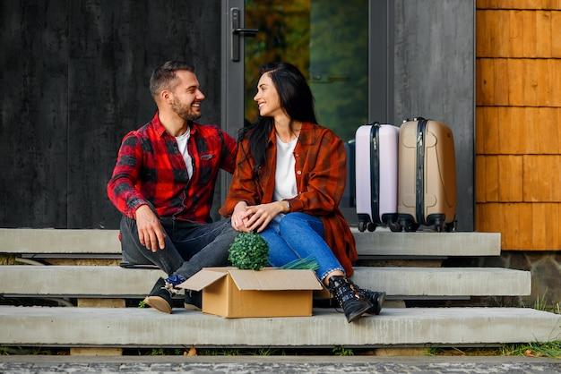 Knappe man en mooie jonge vrouw in stijlvolle kleding zittend op de trappen van het huis en kijken met liefde elkaar tijdens verhuizing naar het nieuwe huis.