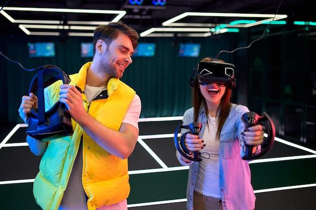 Knappe man en mooie jonge vrouw met een bril van virtual reality. vr, games, entertainment, toekomstig technologieconcept. koppel met virtual reality-headset die samen plezier heeft.