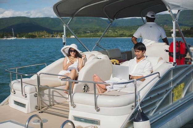 Knappe man en vrouw aan dek van jacht met mobiele telefoon en laptop