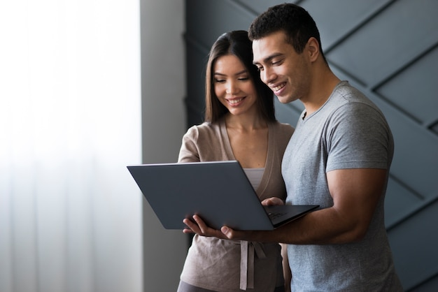 Knappe man en vrouw die aan laptop werkt