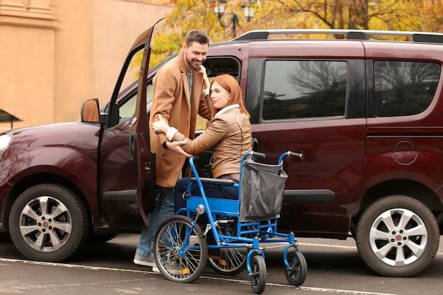 Knappe man en vrouw in rolstoel in de buurt van auto