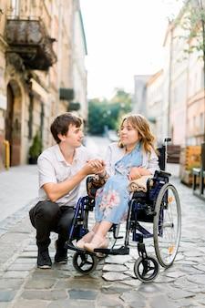 Knappe man en vrouw in rolstoel kijken elkaar op straat. mooi paar in een stoel die samen in de stad loopt