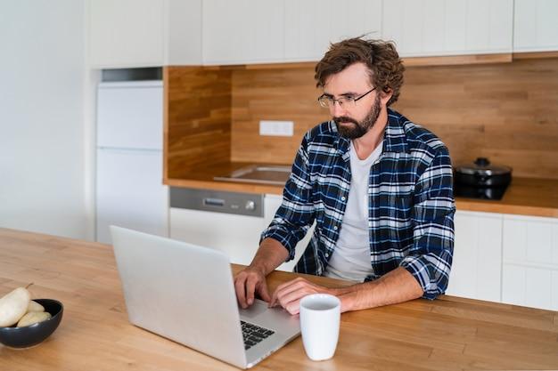 Knappe man freelancer met behulp van laptop online werken vanuit huis studeren