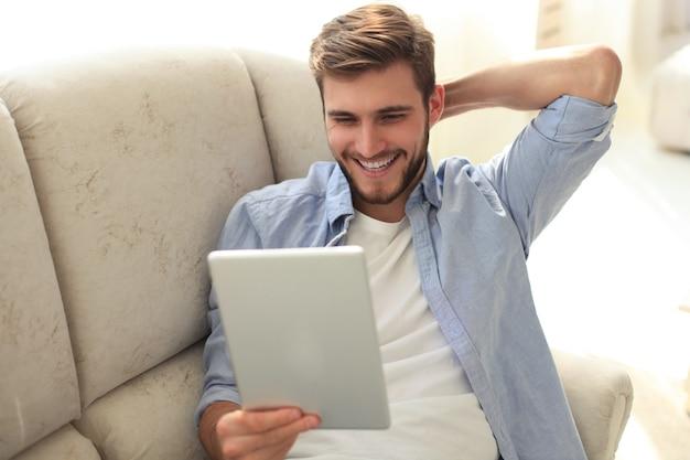 Knappe man gebruikt een digitale tablet en glimlacht terwijl hij thuis op de bank rust.