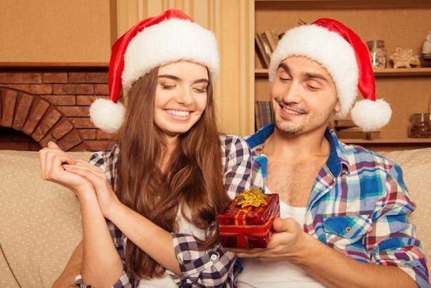 Knappe man geeft een cadeau aan zijn vriendin voor kerstmis
