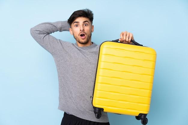 Knappe man geïsoleerd op blauwe muur in vakantie met reiskoffer en verrast