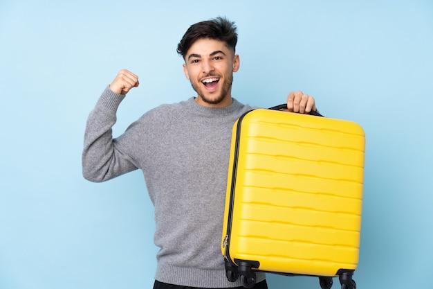 Knappe man geïsoleerd op blauwe muur in vakantie met reiskoffer