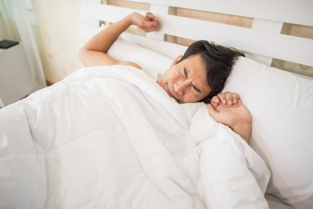 Knappe man gelukkig wakker worden in het bed