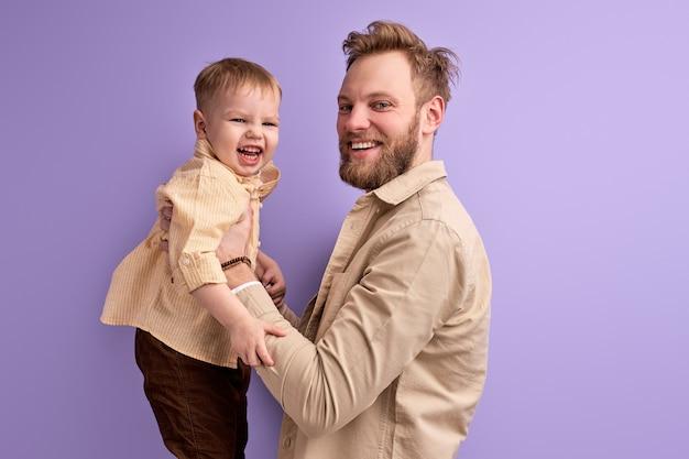 Knappe man geniet van tijd doorbrengen met zoon, in casual outfit poseren spelen geïsoleerd op paarse muur