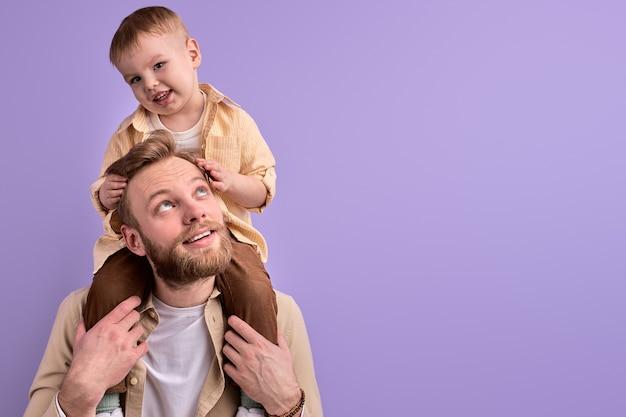 Knappe man geniet van tijd doorbrengen met zoon, in casual outfit poseren spelen. papa die jongen op hals houdt.