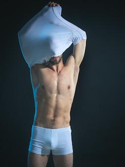 Knappe man, gespierde macho, bodybuilder, met sexy, spier torso, verwijdert t-shirt. aantrekkelijke man in ondergoed toont buikspieren opstijgen t-shirt. brute macho, gekleed in wit ondergoed.