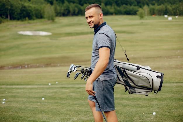 Knappe man golfen op een golfbaan