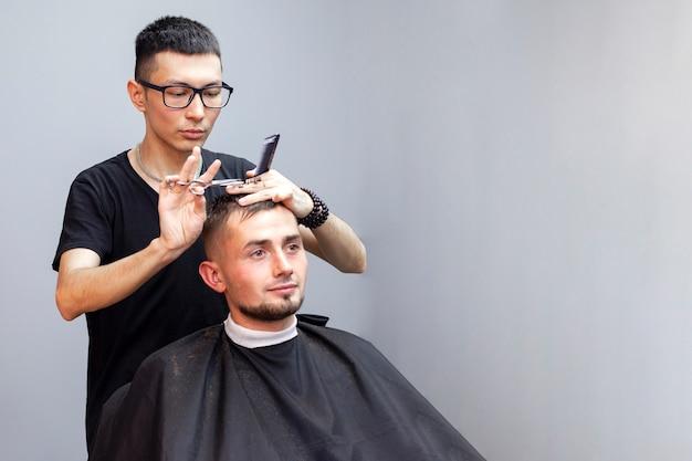 Knappe man heeft een kapsel bij de kapper, een jonge kazachse kapper knipt handmatig met een schaar en een kam, de meester maakt een kort kapsel tegen een grijze muur